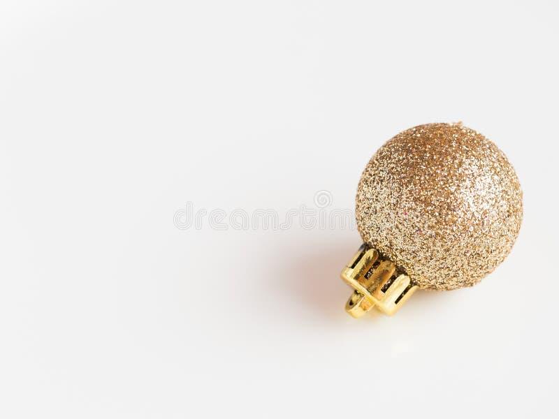 Detalhe de um ornamento brilhante e altivo do Natal do ouro do brilho no fundo branco imagem de stock royalty free