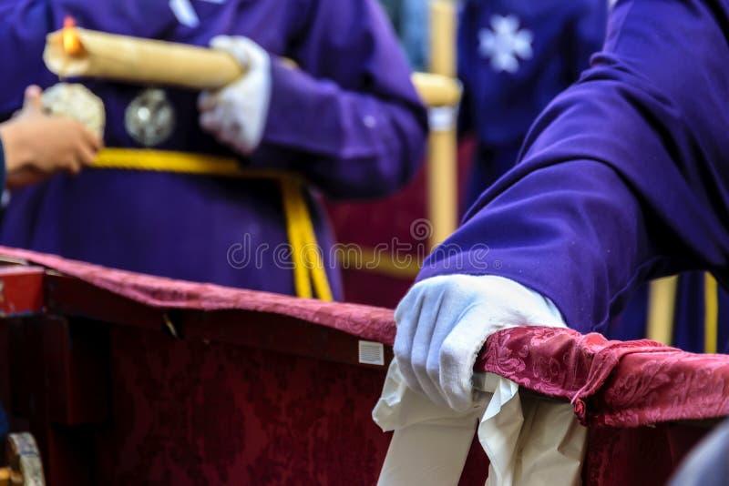 Detalhe de um penitente que descansa ao esperar para recomeçar o março na procissão de Jesus o Nazarene em Huelva, Espanha imagem de stock