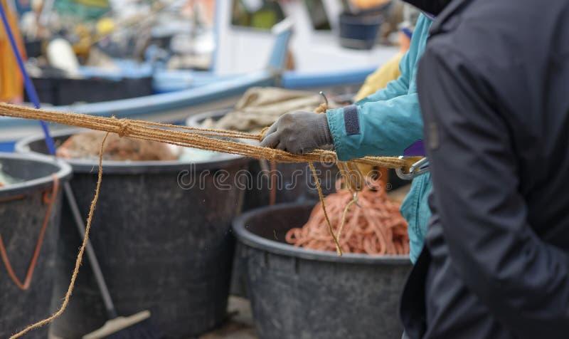 detalhe de um pescador que repara a rede imagens de stock