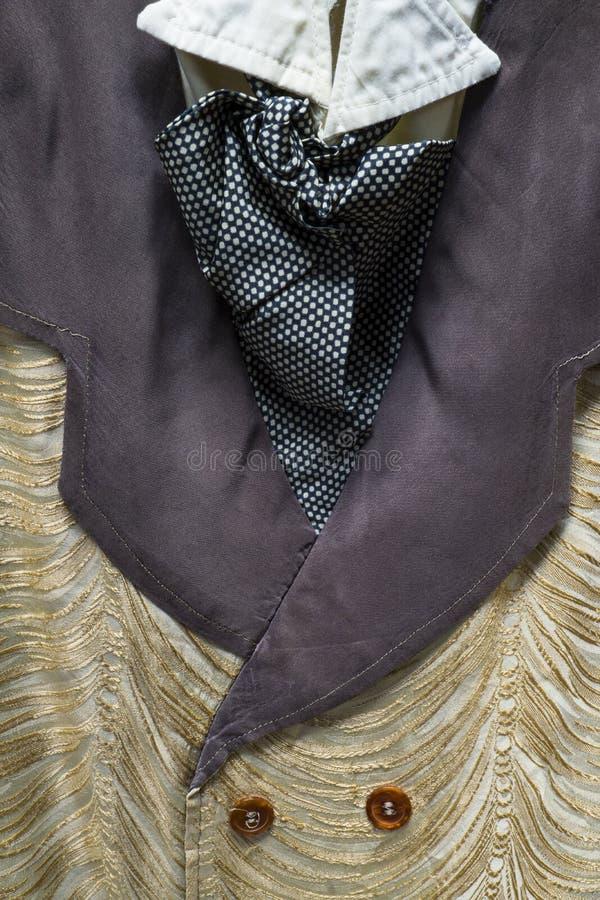 Detalhe de uma antiguidade, terno dos homens ocidentais do estilo com uma veste extravagante e laço imagem de stock