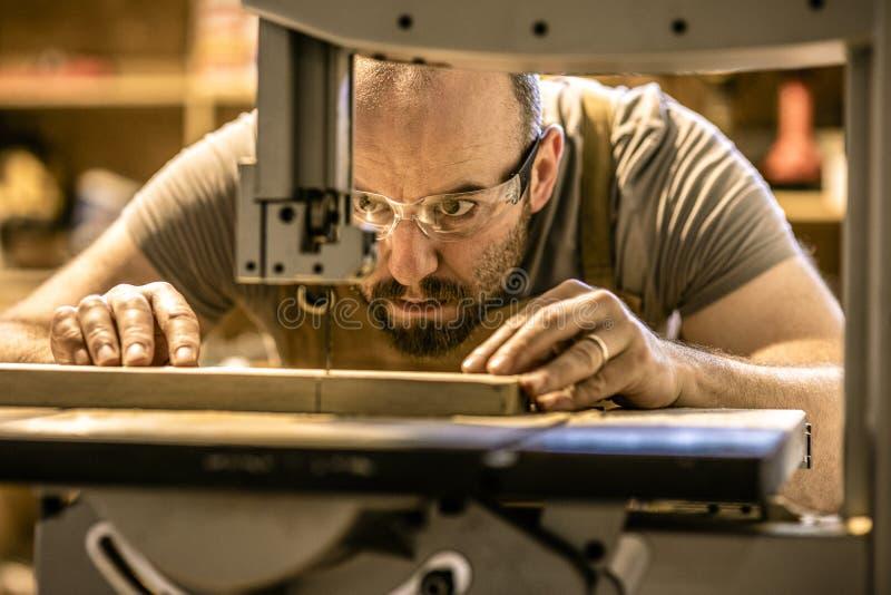 Detalhe de uma intenção do carpinteiro em cortar uma parte de madeira com precisão imagem de stock royalty free
