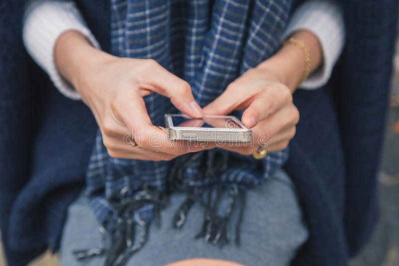 Detalhe de uma menina bonita que texting nas ruas da cidade fotos de stock