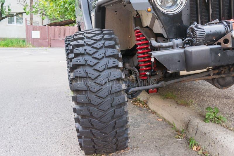 Detalhe de veículo offroad que mostra o pneu grande e a suspensão de bobina vermelha fotografia de stock