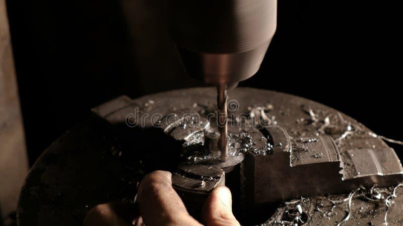 Detalhe do aço de perfuração do metalúrgico Close-up do bocado de broca com aparas do metal Trabalho mecânico na oficina elétrico imagem de stock