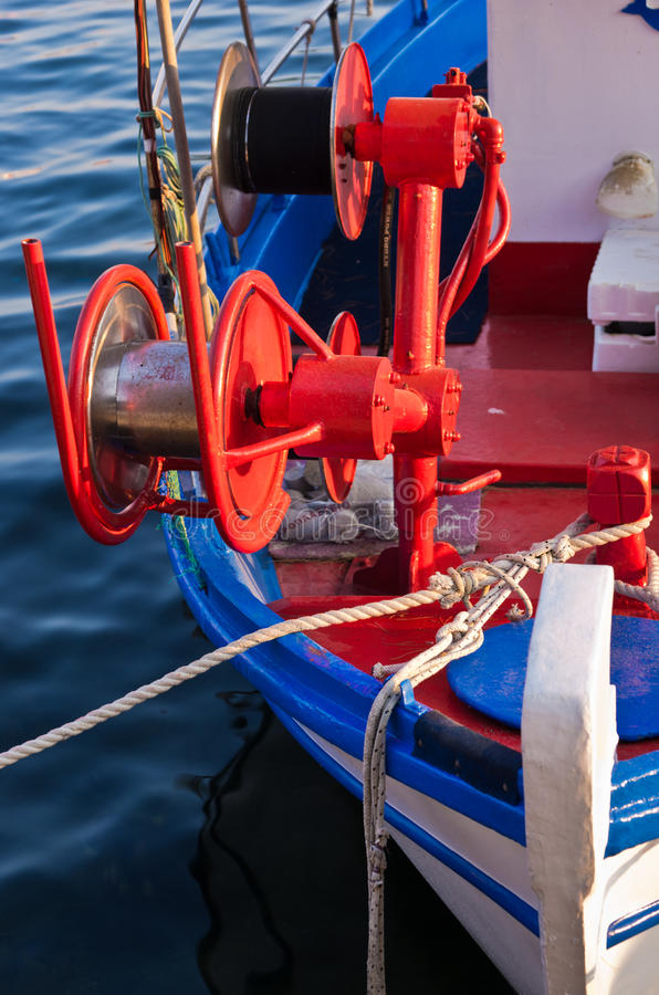 Detalhe do barco de pesca com maquinaria colorida vermelha da pesca no por do sol em Porto Koufo, Sithonia foto de stock royalty free