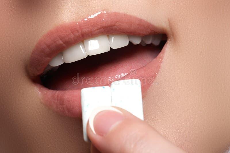 Detalhe do close up de mulher que põe a pastilha elástica cor-de-rosa em sua boca imagem de stock