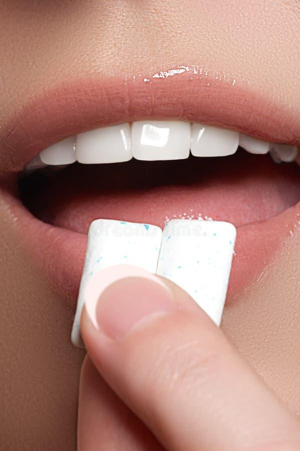 Detalhe do close up de mulher que põe a pastilha elástica cor-de-rosa em sua boca Pastilha elástica, comendo, mulheres Feche acim foto de stock