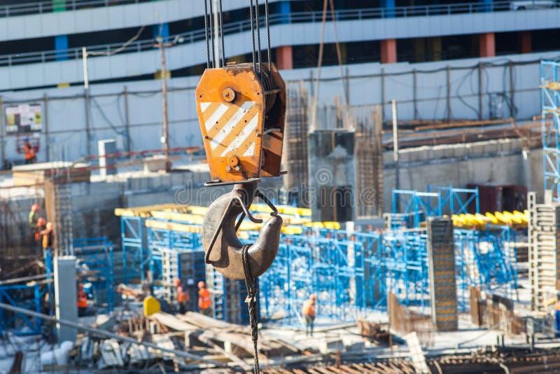 Detalhe do gancho de levantamento do guindaste de torre contra a construção de uma grande construção comercial fotografia de stock