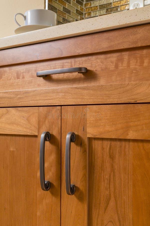 Detalhe dos armários de madeira de alta qualidade com a bancada de bronze do hardware e do quartzo do armário na cozinha home con fotografia de stock