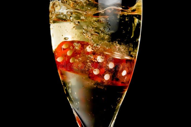 Detalhe dos dados vermelhos que deixam cair na flauta de champanhe imagem de stock
