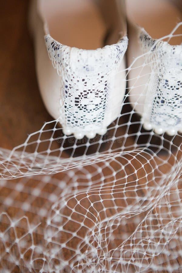 Detalhe dos saltos de um par das sapatas brancas do vintage aparadas com laço e pérolas fotos de stock