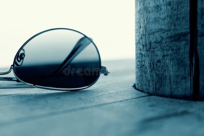 Detalhe espelhado dos óculos de sol no fundo de madeira Conceito da forma em ciano imagem de stock royalty free