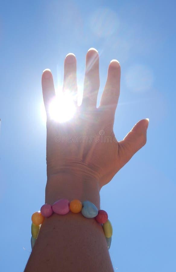 Detalhe a fotografia de cor de raios de travamento do sol da mão da mulher e do céu azul imagens de stock