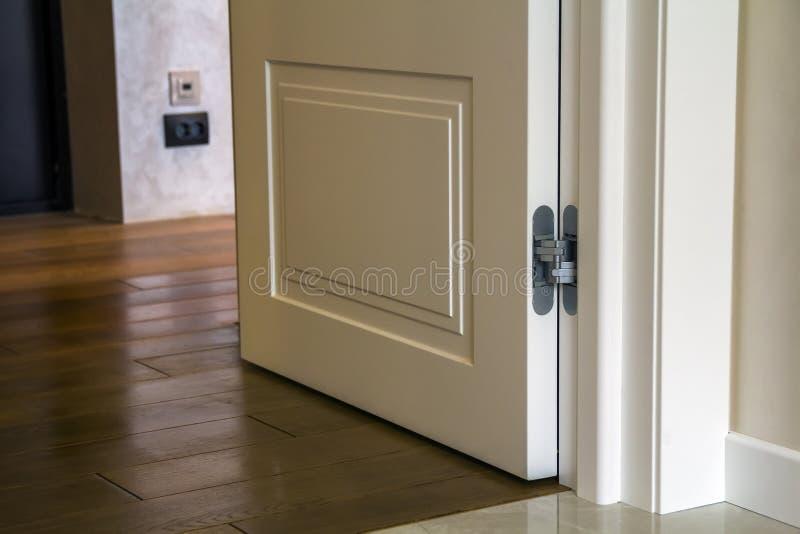 Detalhe interior da casa moderna com o assoalho de parquet de madeira e a porta branca Apartamento após o close-up da renovação imagens de stock royalty free