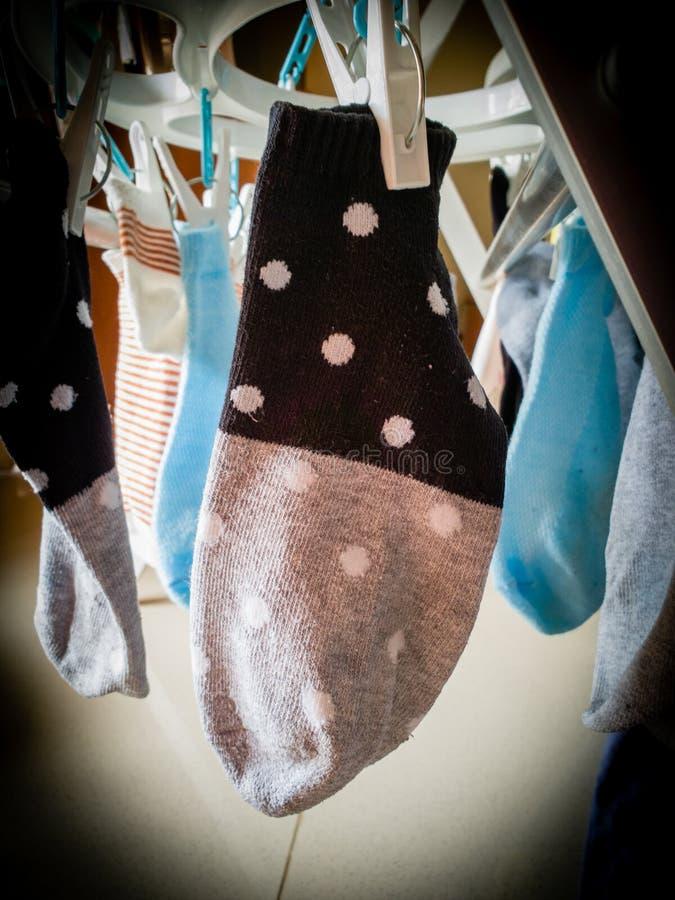 Detalhe macro de fim tecido da peúga do tornozelo acima, secando em uma cremalheira da lavanderia, com fundo borrado de outras pe imagem de stock royalty free