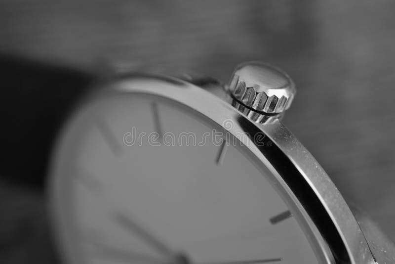 Detalhe macro preto e branco de um grupo recortado dourado da coroa no relógio folheado a ouro como um símbolo do relógio luxuoso imagem de stock