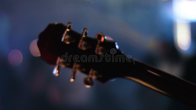 Detalhe a metragem do headstock da guitarra que é jogado pelo músico em um concerto Povos que dançam em um fundo borrado video estoque