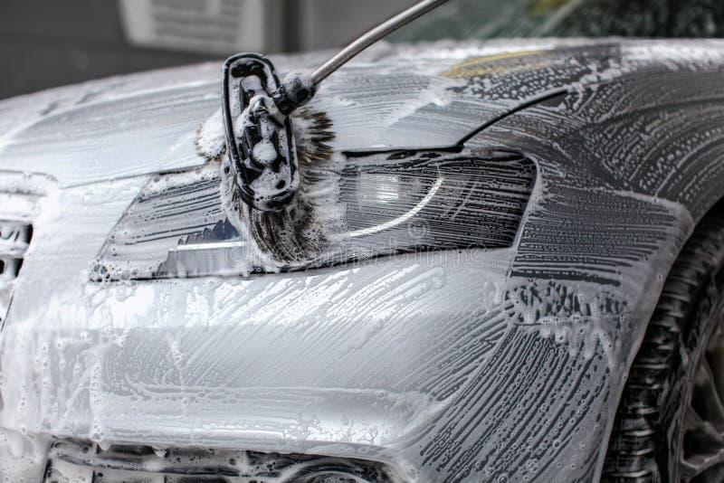 Detalhe na luz dianteira do carro que está sendo lavada com espuma do sabão fotografia de stock royalty free