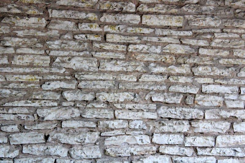 Detalhe na parede exterior de pedra da construção, com testes padrões interessantes e as texturas retratados na habilidade foto de stock