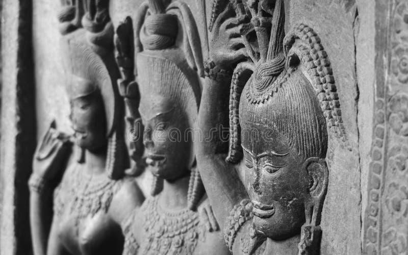 Detalhe nas caras nas paredes do templo de Angkor Wat em Camboja imagens de stock royalty free