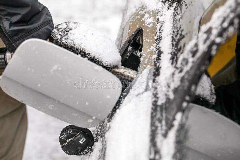Detalhe no homem que reabastece seu carro diesel no inverno, porta do tanque de gás coberta com a neve imagem de stock