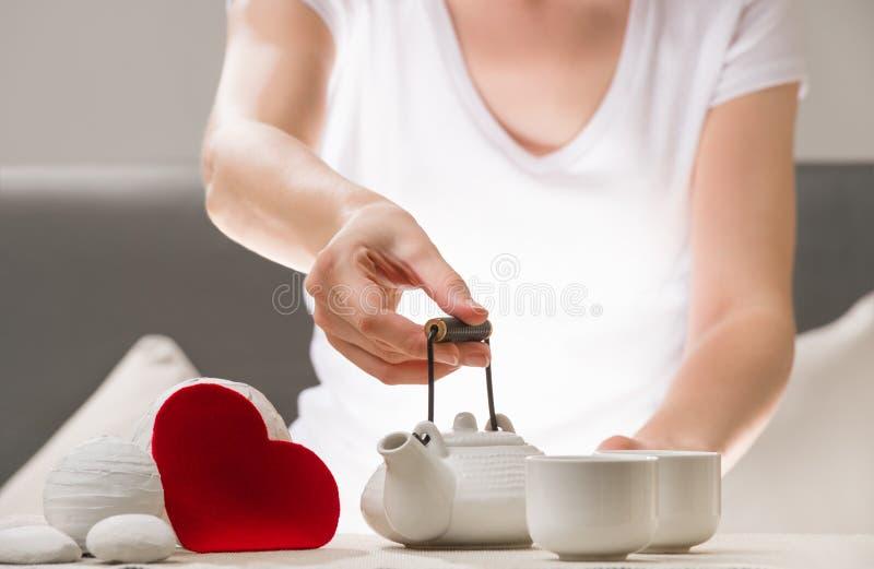 Detalhe o tiro do potenciômetro fêmea e do acolhimento do chá da terra arrendada de braço a joing fotografia de stock