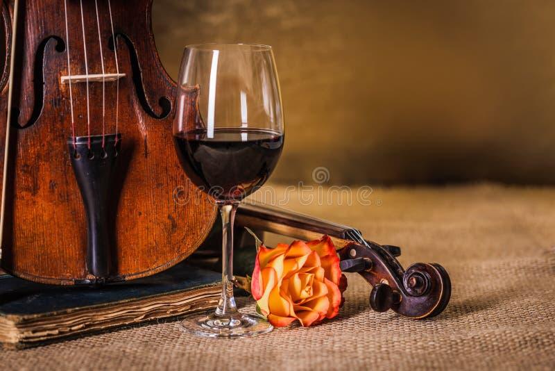 Detalhe velho clássico dos violinos com vidro de vinho tinto imagens de stock royalty free