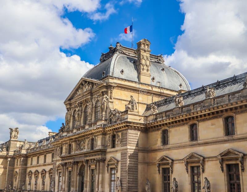 Detalhes arquitetónicos da fachada do palácio do Louvre em Paris, França com a bandeira francesa no telhado Em abril de 2019 fotos de stock royalty free
