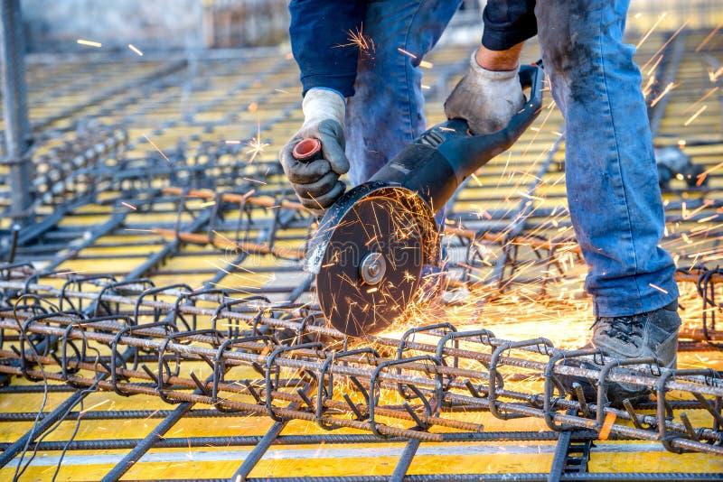 Detalhes da indústria da construção civil - o trabalhador que corta as barras de aço que usam a mitra do moedor de ângulo viu imagens de stock