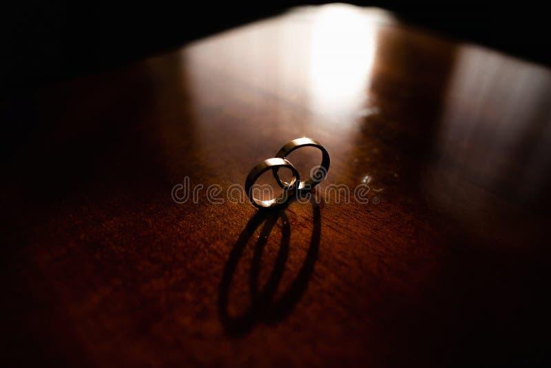 Detalhes da manh? do dia do casamento duas alian?as de casamento do ouro est?o na tabela de madeira marrom fotografia de stock royalty free