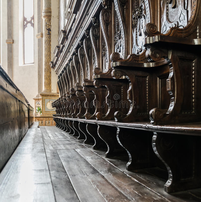 Detalhes de bancos de madeira ao lado do altar de uma igreja medieval fotografia de stock