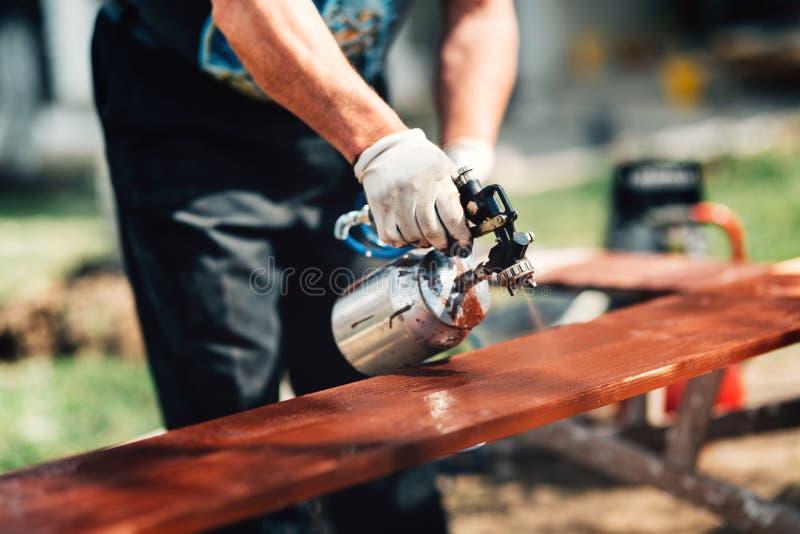 Detalhes de homem que usa a arma ou o aerógrafo de pulverizador para a cerca de pintura Detalhes da carpintaria com carpintaria e imagens de stock