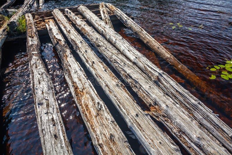 Detalhes de uma ponte destruída de madeira velha através do rio fotos de stock royalty free