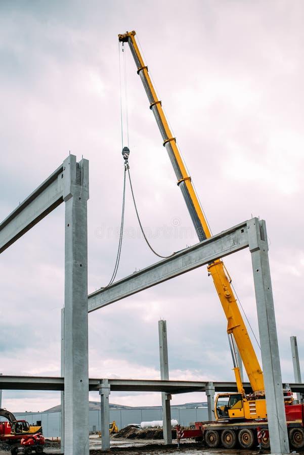 Detalhes do canteiro de obras - crane o levantamento de um feixe do cimento do concreto pré-fabricado ao conjunto de construção fotos de stock royalty free