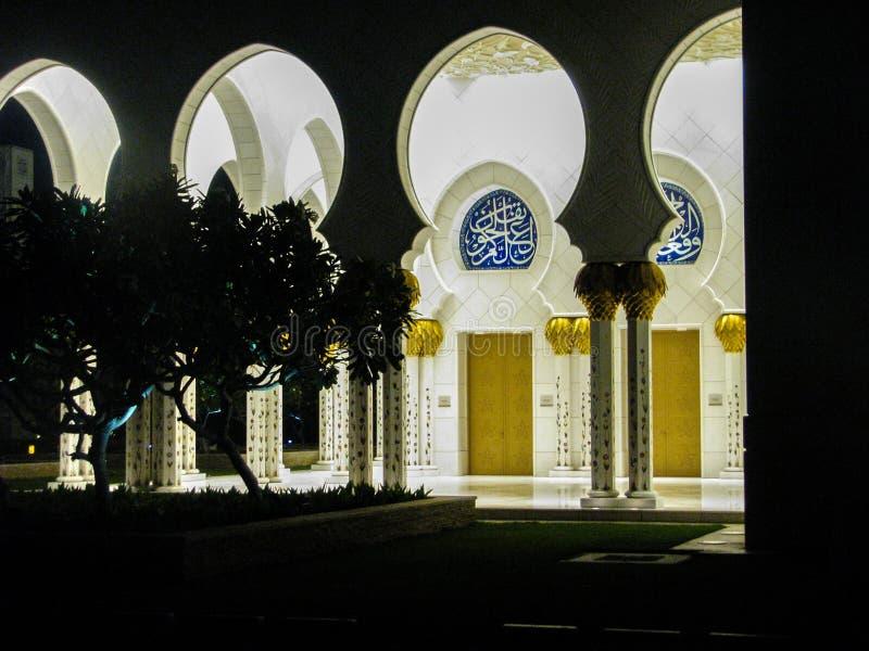 Detalhes e arquitetura bonitos de Abu Dhabi Sheik Zayed Mosque com reflexões na água na noite imagens de stock royalty free