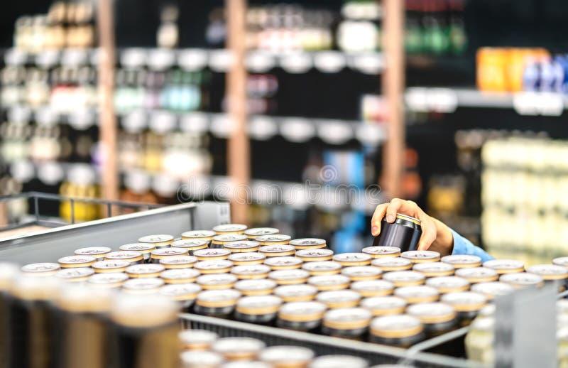 Detalicznego pracownika podsadzkowa półka z napojami w sklepie spożywczym lub kliencie bierze puszkę piwo lub soda obrazy royalty free