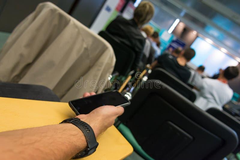 Detalj av affärsmanhanden som rymmer en smart telefon på konferensen royaltyfri foto