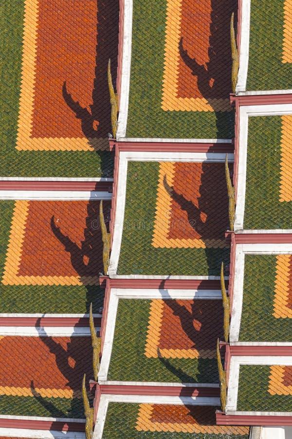 detalj av apelsinen, gulingen och gräsplantaktegelplattorna av thailändsk templ royaltyfri bild