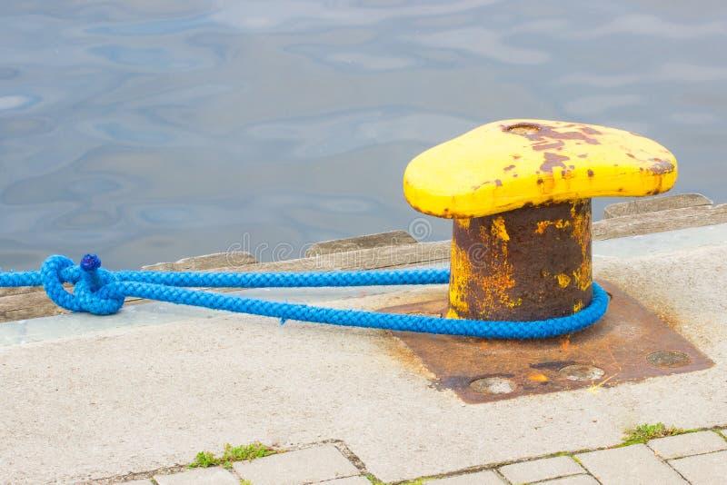 Detalj av att segla, blått rep med den gamla gula förtöja pollaren i port royaltyfri fotografi