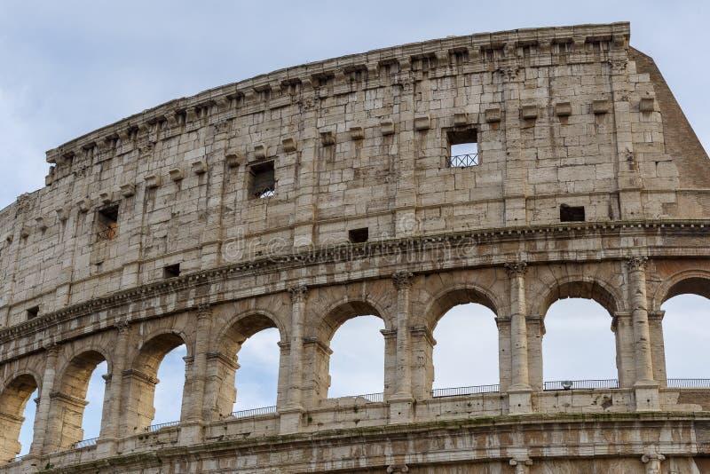 Detalj av Colosseumen, under en blå himmel med vita moln arkivbild