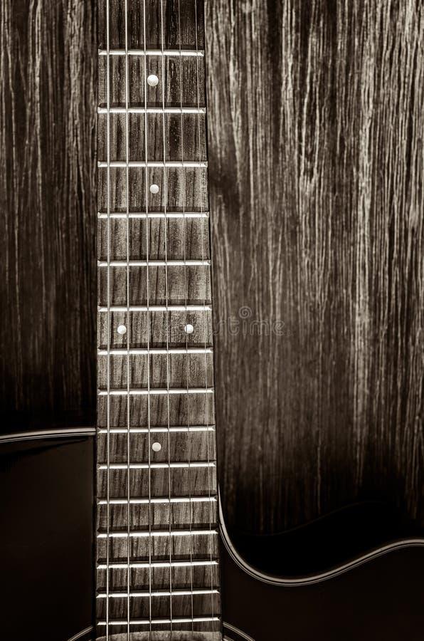 Detalj av den akustiska gitarren i tappningstil på wood bakgrund arkivfoto