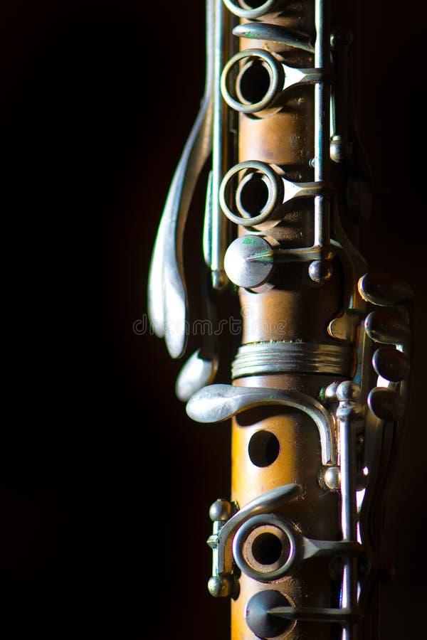 Detalj av den antika klarinetten på en svart bakgrund arkivfoto