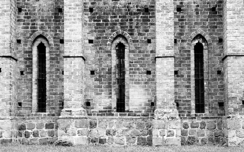 Detalj av den gamla domkyrkakloster med den medeltida stentegelstenväggen och långsträckta fönster i gotisk arkitektur för karakt royaltyfria bilder
