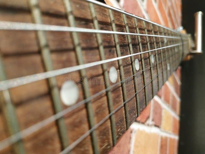 Detalj av den gamla fretboarden av det elektroniska gitarrslutet upp royaltyfri fotografi