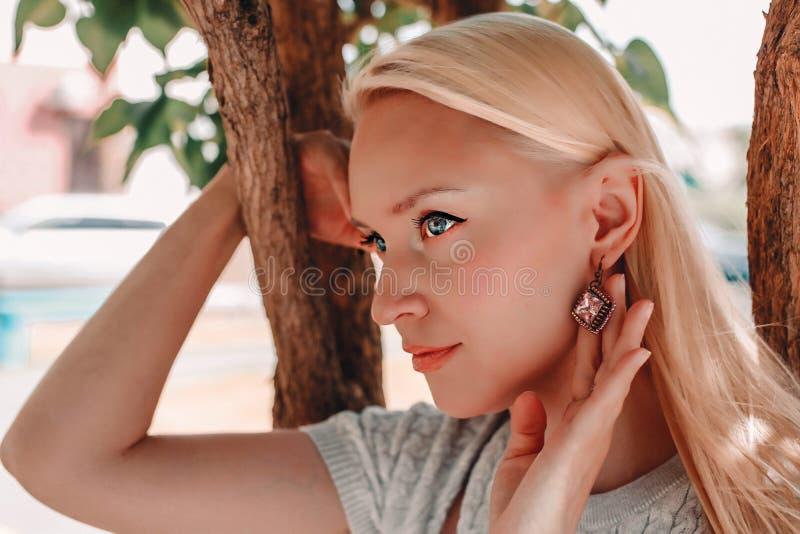 Detalj av den unga blonda kvinnan som bär det härliga lyxiga guld- örhänget fotografering för bildbyråer