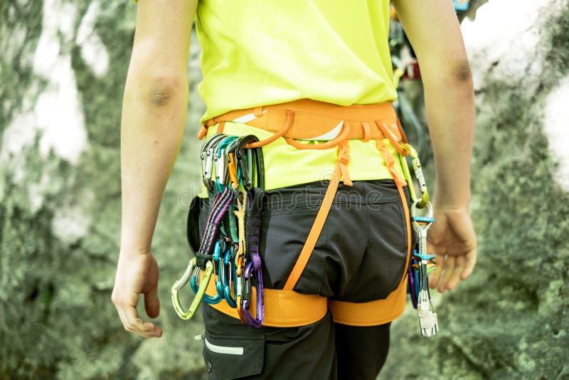 Detalj av den unga mannen som förbereda sig på en klättring och ett anseende a bredvid vagga väggen Utrustning för att klättra på fotografering för bildbyråer