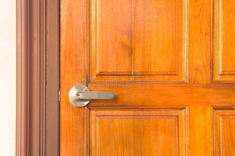 Detalj av det metalliska dörrhandtaget för modern stil på trädörr arkivbild