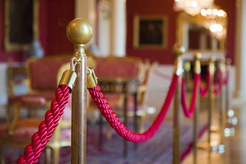 Detalj av det röda repet på ett utställningutrymme - defocused bakgrundsbegreppsbild arkivbild