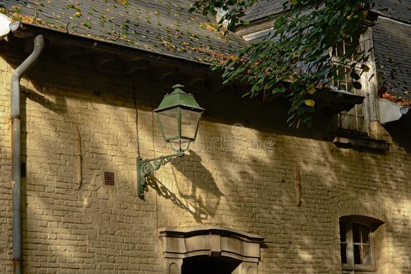 Detalj av en gammal traditionell flemish byggnad med lyktan, lövverk och deras skuggor royaltyfria foton
