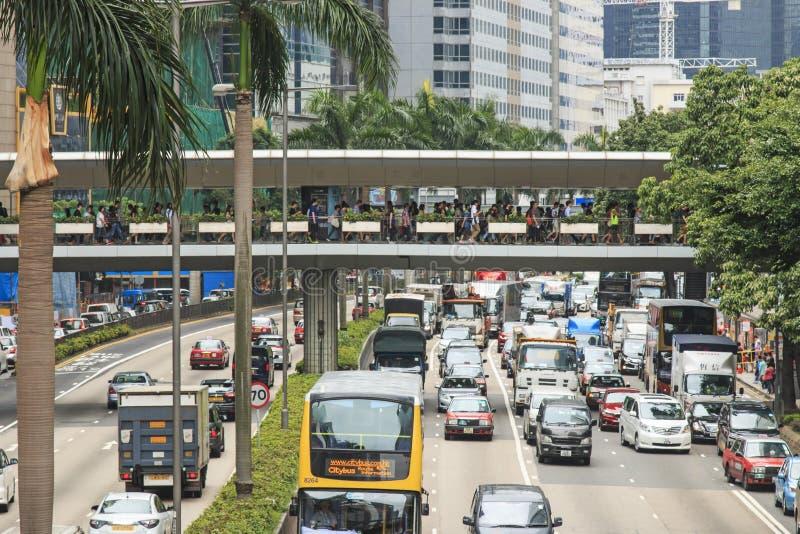 Detalj av en gata i centrala Hong Kong med tung trafik och palmträd i mitten av gatan royaltyfria foton